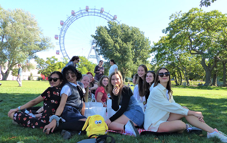Students enjoy lunch in the park with the ferris wheel in the background