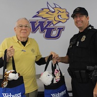 Webster Luke AFB faculty member Herb Kretz presents bags of stuffed animals to Sgt. Jeff Turney (MA '04) for the Glendale, Arizona Police Department's