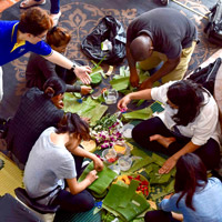 Students work with banana leaves in a workshop to make krathong.
